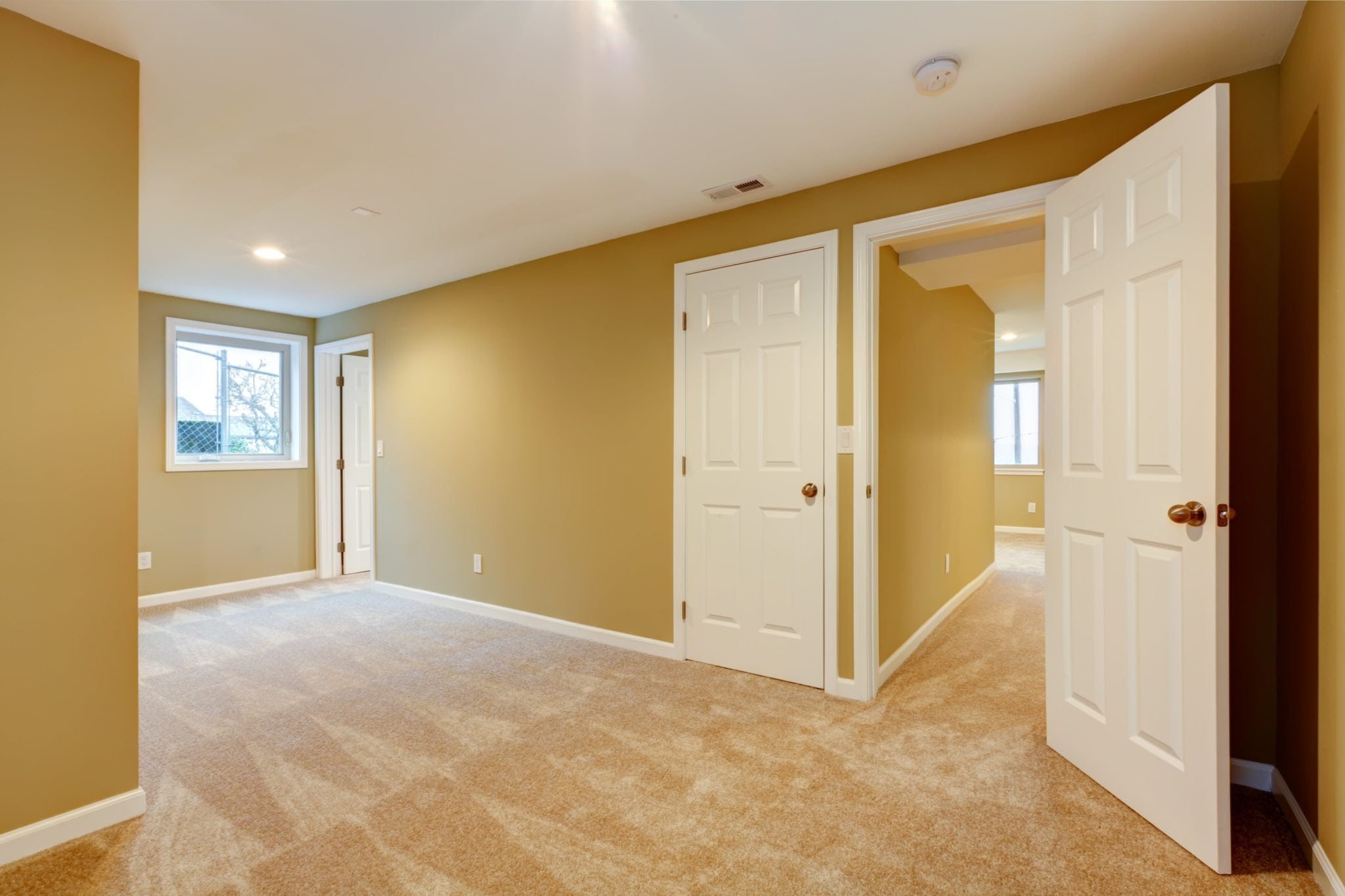 Empty new bedroom with many doors and beige carpet.
